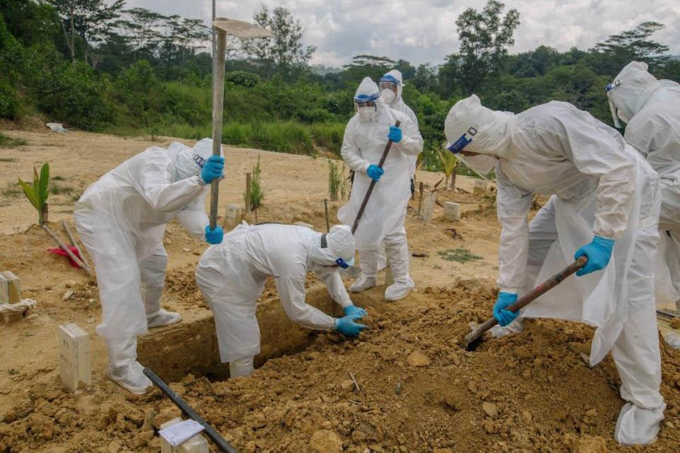 Workers wearing personal protective equipment burying a person who died from Covid-19 at the Muslim cemetery in Gombak June 6, 2021. — Picture by Firdaus Latif
