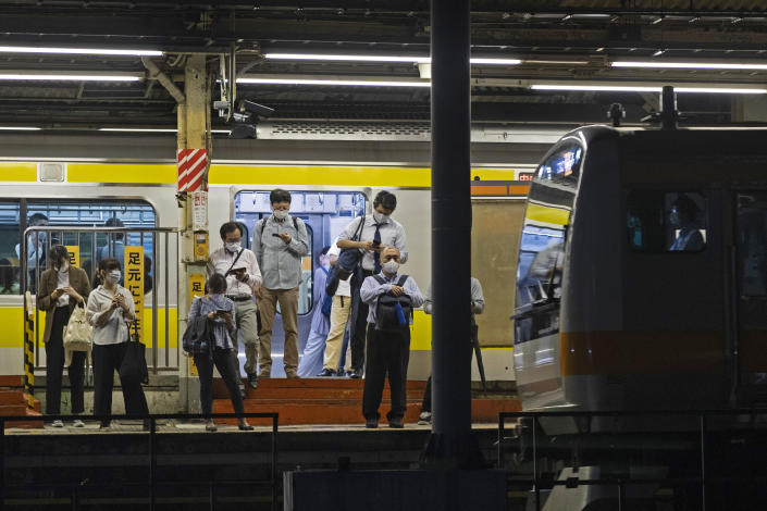 People wearing face masks wait for a train as it approaches a station in Tokyo, Thursday, Sept. 9, 2021. Japan announced Thursday it is extending a coronavirus state of emergency in Tokyo and 18 other areas until the end of September as health care systems remain under severe strain, although new infections have slowed slightly. (AP Photo/Hiro Komae)