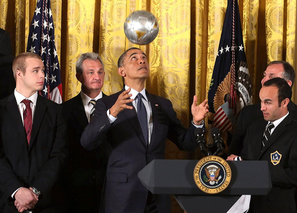"""WASHINGTON, DC - MARCH 26: U.S. President Barack Obama (C) bounces a soccer ball on his head while hosting a ceremony honoring players and coaches from the National Hockey League Stanley Cup-winning Los Angeles Kings and the Major League Soccer champions Los Angeles Galaxy in the East Room of the White House March 26, 2013 in Washington, DC. After the White House honors both California teams, players will participate in a question-and-answer panel with Sam Kass, Assistant White House Chef and Executive Director of first lady Michelle Obama's health program """"Let's Move!"""" (Photo by Chip Somodevilla/Getty Images)"""