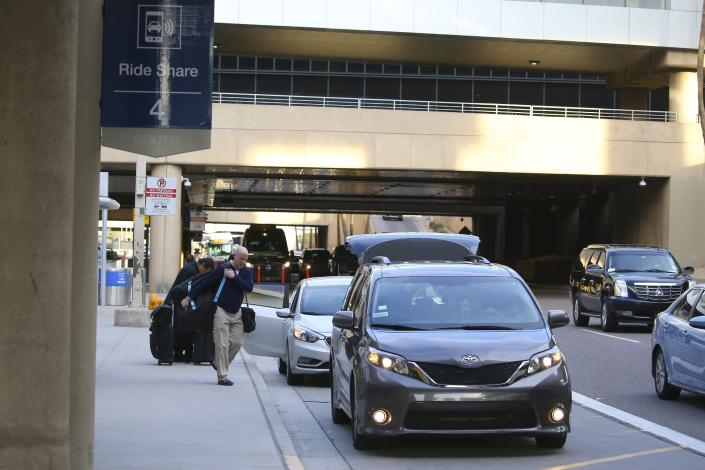 Passengers find their rides at the Ride Share point as they exit Phoenix Sky Harbor International Airport Wednesday, Dec. 18, 2019, in Phoenix. The Phoenix City Council is set to vote on raising fees charged to ride-hailing companies at the airport. If approved Wednesday afternoon, the proposal will increase the current fee from $2.66 per pickup. That would jump to $4 starting Jan. 1 and be applied to drop-offs as well. (AP Photo/Ross D. Franklin)