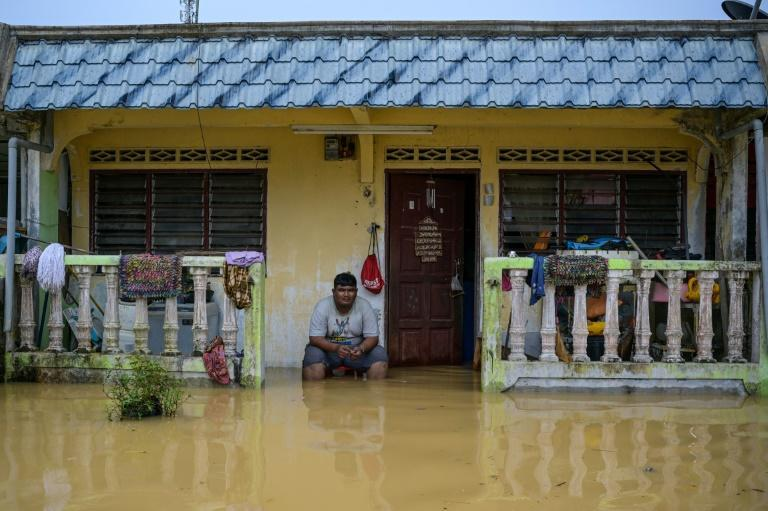 A resident sits outside his home, partially submerged in floodwaters, in Kuala Kaung, near Lanchang in Malaysia's Pahang state