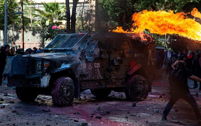 Demonstrators set a riot police vehicle on fire during clashes on the commemoration of the first anniversary of the social uprising in Chile - AFP