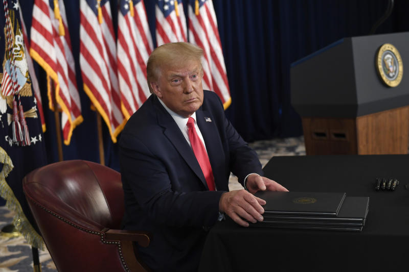 President Donald Trump prepares to sign four executive orders during a news conference at the Trump National Golf Club in Bedminster, N.J., Saturday, Aug. 8, 2020. Seizing the power of his podium and his pen, Trump on Saturday moved to bypass the nation's elected lawmakers as he claimed the authority to defer payroll taxes and extend an expired unemployment benefit after negotiations with Congress on a new coronavirus rescue package collapsed.(AP Photo/Susan Walsh)