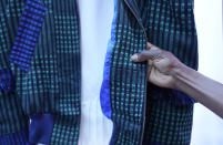 Fashion designer Nyny touches her creation, part of the Black Lives Matter Spring Summer 2022 collective fashion event, unveiled during the Milan Fashion Week in Milan, Italy, Tuesday, Sept. 21, 2021. (AP Photo/Antonio Calanni)