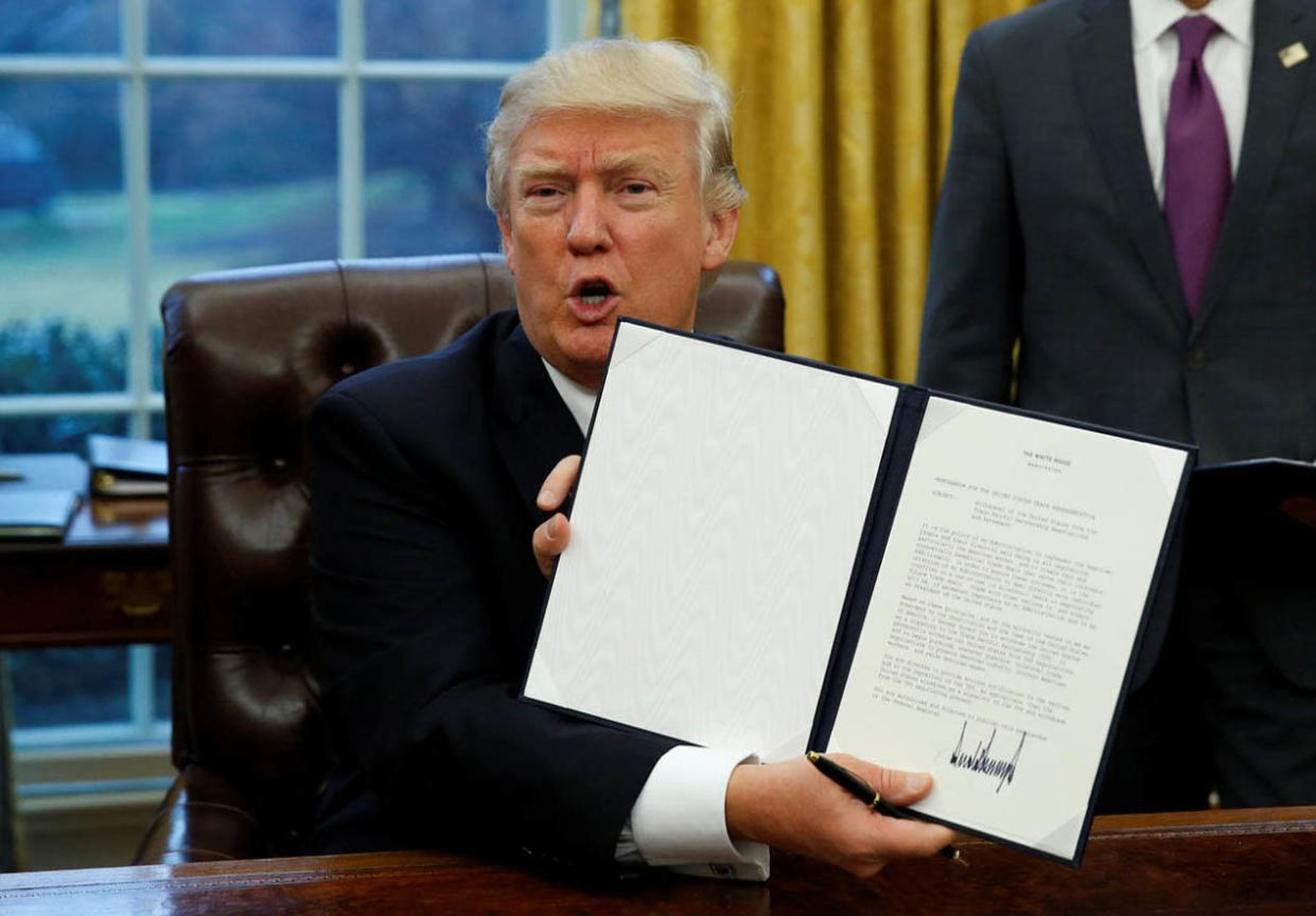 President Trump with an executive order that withdraws the United States from the Trans-Pacific Partnership, Jan. 23, 2017. (Photo: Kevin Lamarque/Reuters)