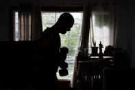 Christian Hainds works out at his home in Hammond, Ind., Monday, June 7, 2021. Health officials have warned since early on in the pandemic that obesity and related conditions such as diabetes were risk factors for severe COVID-19. It wasn't until he was diagnosed as diabetic around the start of the pandemic that he felt the urgency to make changes. Hainds lost about 50 pounds during the pandemic, and at 180 pounds and 5 feet, 11 inches tall is no longer considered obese. (AP Photo/Shafkat Anowar)