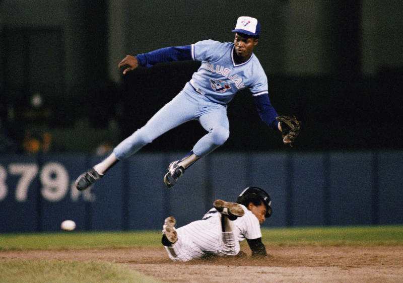 FILE - In this Sept. 18, 1987, file photo, New York Yankees' Rickey Henderson, bottom, steals second base below Toronto Blue Jays shortstop Tony Fernndez during a baseball game in New York. Fernndez, a stylish shortstop who made five All-Star teams during his 17 seasons in the major leagues and helped the Blue Jays win the 1993 World Series, died Sunday, Feb. 16, 2020, after complications from a kidney disease. He was 57. (AP Photo/G. Paul Burnett, File)