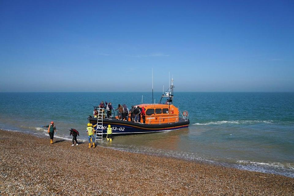 A group of people thought to be migrants are brought ashore from the local lifeboat at Dungeness in Kent (Gareth Fuller/PA) (PA Wire)