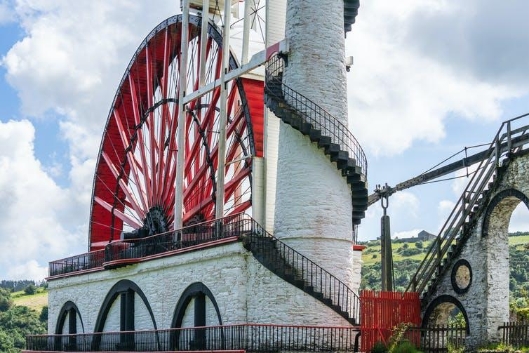 A large red and white wheel next to a tower.