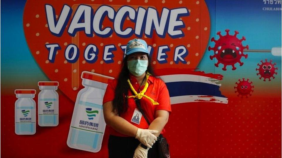 A Thai health volunteer stands in front of a campaign banner for Chinese made Sinopharm vaccine during a mass vaccination drive for disabled and disadvantaged people in Bangkok, Thailand, 25 June 2021.
