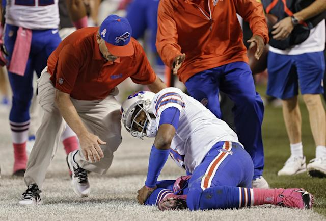 A trainer rushes to help Buffalo Bills quarterback EJ Manuel after he was injured on a third-quarter run against the Cleveland Browns in the third quarter of an NFL football game Thursday, Oct. 3, 2013, in Cleveland. (AP Photo/Tony Dejak)
