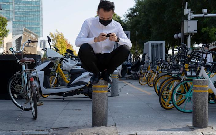 A man rests on a barrier as he waits to cross a road in Beijing - AP
