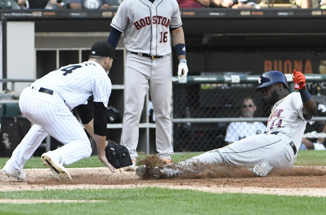 Houston Astros' Yordan Alvarez (44) is safe at home plate as Chicago White Sox starting pitcher Dylan Cease (84) makes a late tag during the sixth inning of game one of a baseball doubleheader, Tuesday, Aug. 13, 2019, in Chicago. (AP Photo/David Banks)