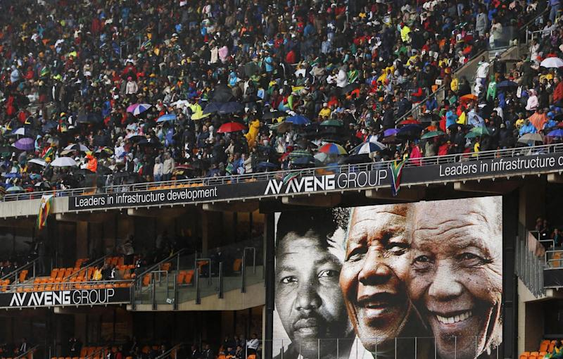 Faces of Nelson Mandela through the ages are shown on a big screen during the memorial service for former South African president Nelson Mandela at the FNB Stadium in Soweto, near Johannesburg, South Africa, Tuesday Dec. 10, 2013. (AP Photo/Ben Curtis)