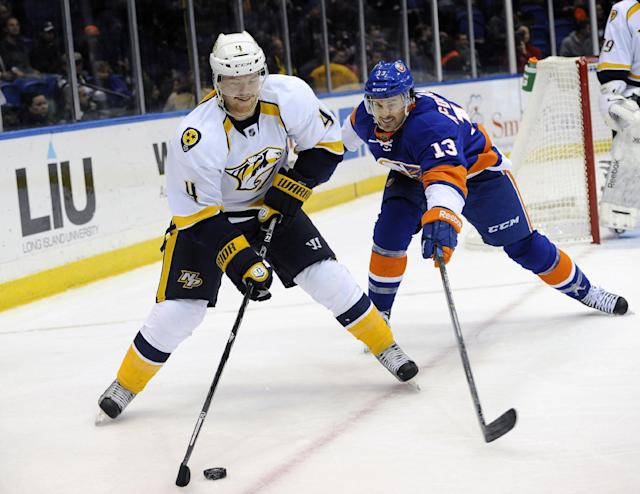 Nashville Predators' Ryan Ellis (4) and New York Islanders' Colin McDonald (13) chase the puck around the boards during the second period of an NHL hockey game on Tuesday, Nov. 12, 2013, in Uniondale, N.Y. (AP Photo/Kathy Kmonicek)