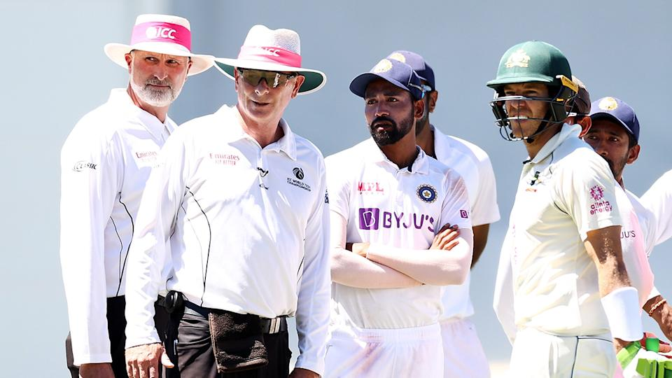 Umpires Paul Reiffel and Paul Wilson, Mohammed Siraj and Tim Paine look at the crowd during a suspension in play following a complaint regarding spectators during day four of the Third Test match between Australia and India at the SCG. (Photo by Cameron Spencer/Getty Images)