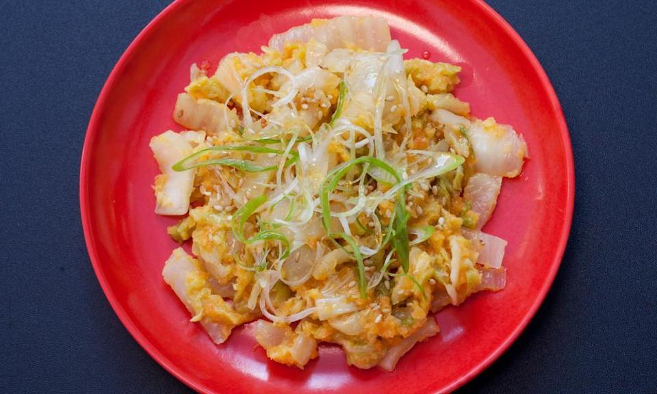 A round red plate with golden kimchi