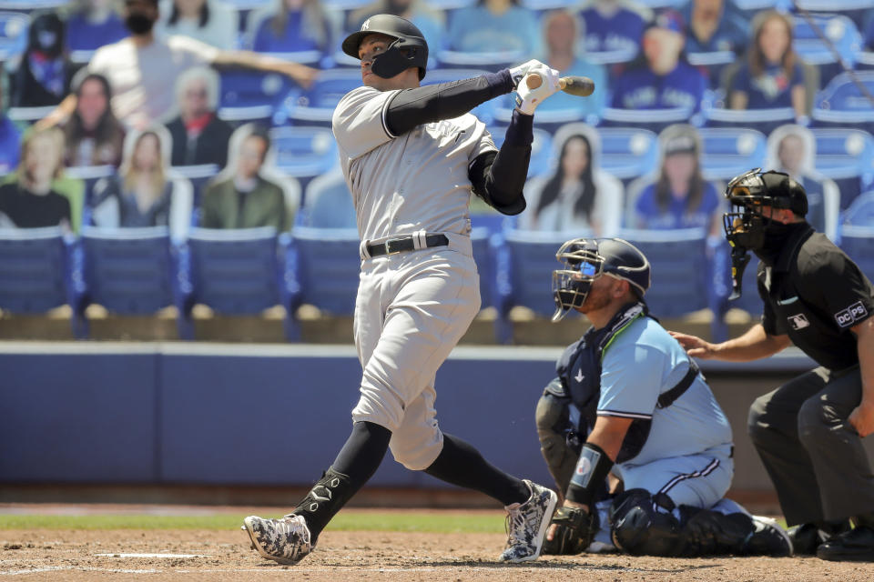 New York Yankees' Aaron Judge follows through on his second solo home run as Toronto Blue Jays catcher Alejandro Kirk and home plate umpire Tripp Gibson look on during the fourth inning of a baseball game Wednesday, April 14, 2021, in Dunedin, Fla. (AP Photo/Mike Carlson)