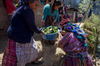 Women carry a bowl filled with vegetable to be cooked at the wake of Rubelsy Tomas Isidro, one of the Guatemalan migrants who was killed near the U.S.-Mexico border in January, at his home in Comitancillo, Guatemala, Saturday, March 13, 2021. Thousands of residents of this Guatemalan town turned out Friday night amid tears and applause to receive the remains of 16 of their own, found piled in a charred pickup truck in Camargo, across the Rio Grande from Texas. (AP Photo/Moises Castillo)