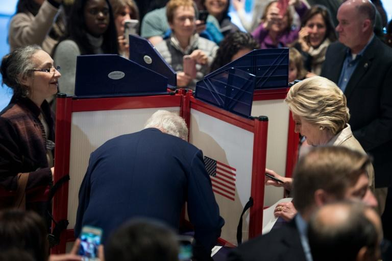 Former US President Bill Clinton (L) and Democratic presidential nominee Hillary Clinton (R) vote at Douglas G. Griffin School November 8, 2016 in Chappaqua, New York