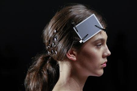 A model uses a playing card to keep her hair in place as she walks the runway during a rehearsal before a presentation of the Honor Spring/Summer 2014 collection during New York Fashion Week
