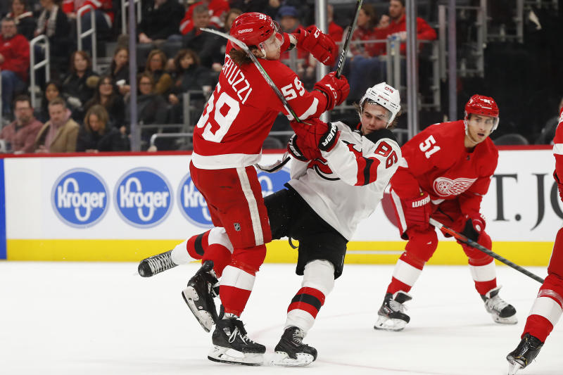 Detroit Red Wings left wing Tyler Bertuzzi (59) checks New Jersey Devils center Jack Hughes (86) off the puck in the second period of an NHL hockey game Tuesday, Feb. 25, 2020, in Detroit. (AP Photo/Paul Sancya)
