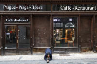 FILE - In this Sunday, Oct. 11, 2020 file photo, a beggar kneels in front of a closed restaurant in downtown Prague, Czech Republic. The coronavirus pandemic is gathering strength again in Europe and, with winter coming, its restaurant industry is struggling. The spring lockdowns were already devastating for many, and now a new set restrictions is dealing a second blow. Some governments have ordered restaurants closed; others have imposed restrictions curtailing how they operate. (AP Photo/Petr David Josek, File)