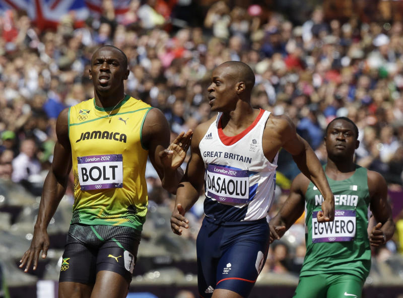 Jamaica's Usain Bolt, left, reacts after winning ahead of Nigeria's Ogho-Oghene Egwero, right, and Britain's James Dasaolu in a men's 100-meter heat during the athletics in the Olympic Stadium at the 2012 Summer Olympics, London, Saturday, Aug. 4, 2012. (AP Photo/Lee Jin-man)