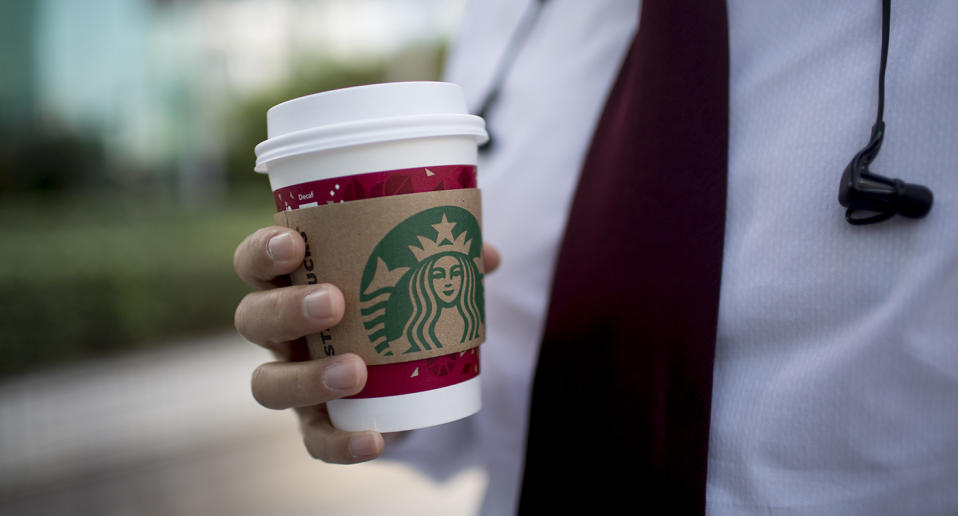 A man holds a disposable Starbucks coffee cup