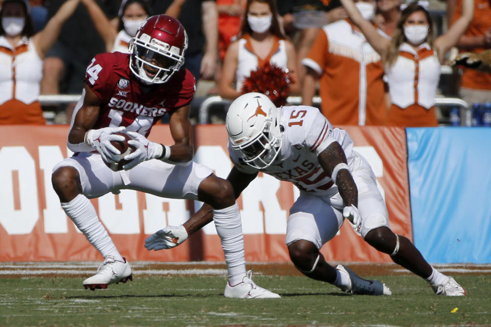 Oklahoma wide receiver Charleston Rambo (14) catches a pass in front of Texas defensive back Chris Brown (15) during an NCAA college football game in Dallas, Saturday, Oct. 10, 2020. (AP Photo/Michael Ainsworth)