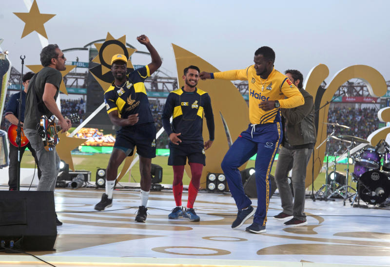FILE - In this March 25, 2018 file photo, West Indies cricketers Darren Sammy, right, Andre Fletcher, second left, and Pakistani cricketer Hassan Ali, center, dance during a music show prior to start of the Pakistan Super League final cricket match at National stadium, in Karachi, Pakistan. The Pakistan Super League is not like any other domestic Twenty20 cricket league around the world. It can't compete financially with the lucrative Indian Premier League in terms of player payments, yet it's a dream for Pakistani cricketer to be part of it. For the Pakistan Cricket Board, the PSL is a pathway to ultimately bring foreign teams back to Pakistan and resume fully-fledged international cricket on home soil. (AP Photo/Fareed Khan, File)