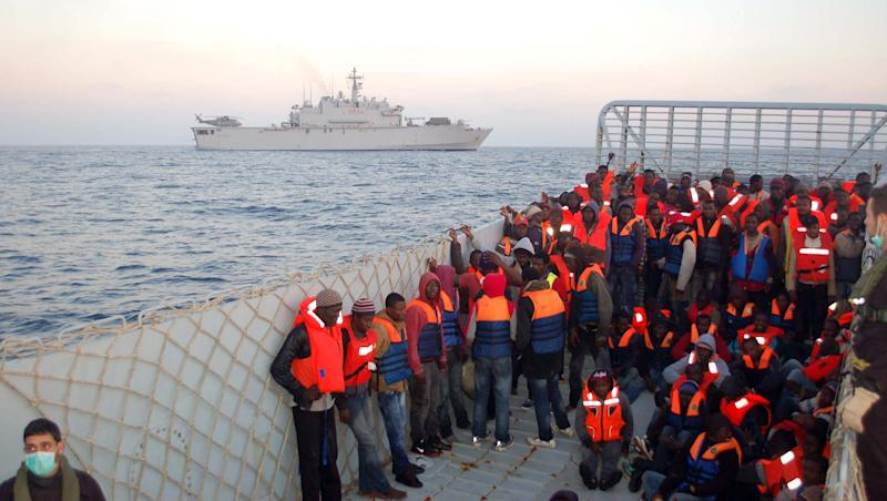 In this photo released by the Italian Navy Thursday, March 20, 2014, rescued migrants are about to be boarded on the San Giusto ship, background, along the Mediterranean sea. Italian authorities say they have rescued more than 4,000 would-be migrants at sea over the past four days as the war in Syria and instability in Libya spawn new waves of refugees. The numbers of migrants reaching Italian shores generally rises as warm weather and calm seas make the Mediterranean Sea crossing from North Africa easier. But the U.N. refugee agency says the 2014 numbers represent a 300 percent increase over the same period in 2013. (AP Photo/Italian Coast guard)