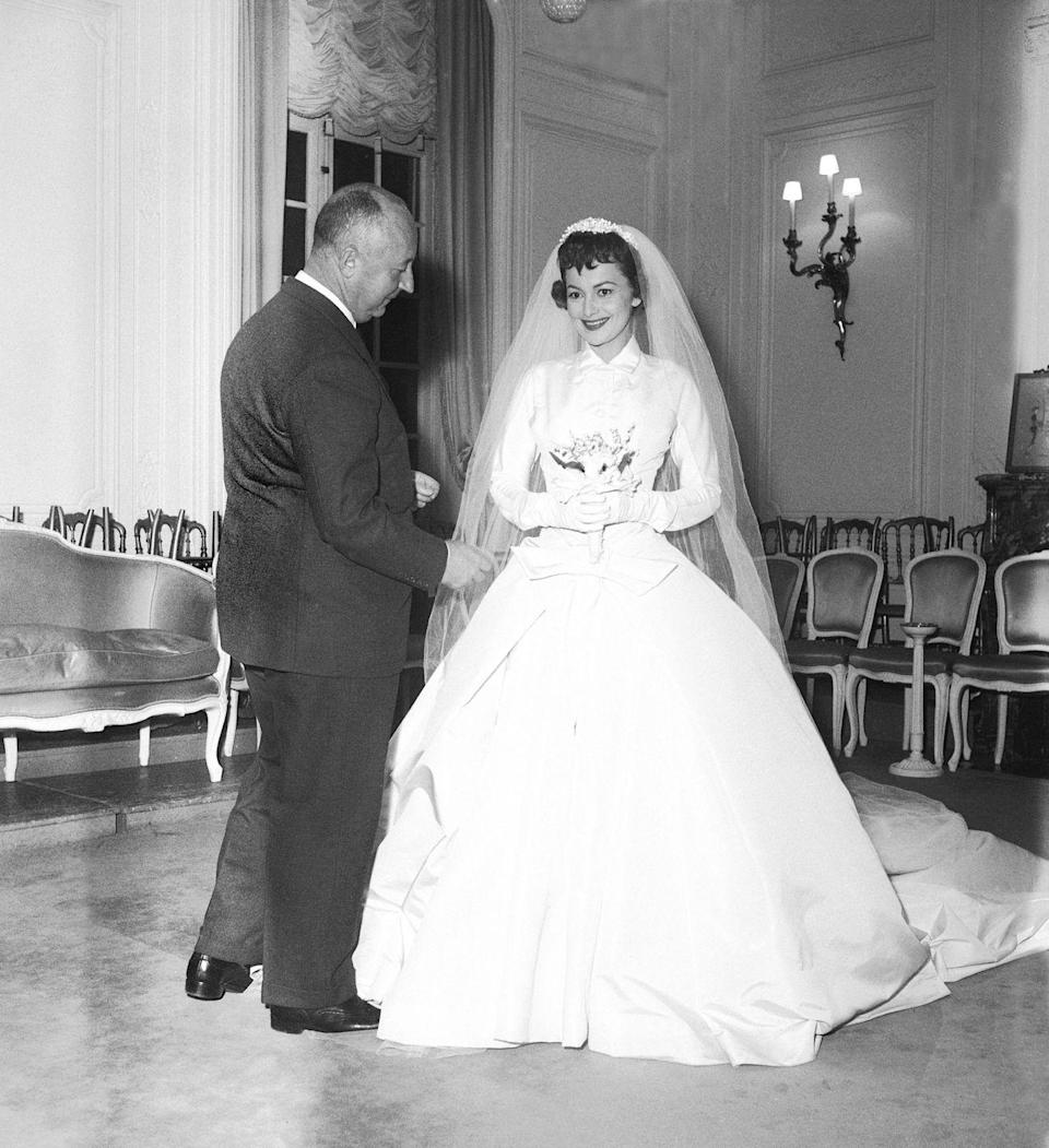 """<p>Actress Olivia de Havilland donned a Christian Dior wedding dress with a high neck and long sleeves while filming the romantic comedy <a href=""""http://www.imdb.com/title/tt0048944/"""" rel=""""nofollow noopener"""" target=""""_blank"""" data-ylk=""""slk:The Ambassador's Daughter"""" class=""""link rapid-noclick-resp""""><em>The Ambassador's Daughter</em></a>, which was released the following year.</p>"""
