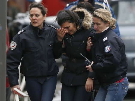 Police take charge of a woman at the scene of a shooting in the street of Montrouge near Paris January 8, 2015. REUTERS/Charles Platiau