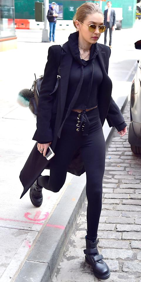 <p>Hadid was snapped making her way through the Big Apple in a cropped black hoodie and matching high-waisted leggings that showed off her super fit physique. She topped off her look with a long coat, black leather sneakers, gold Linda Farrow sunnies, and a pompom-adorned backpack. </p>