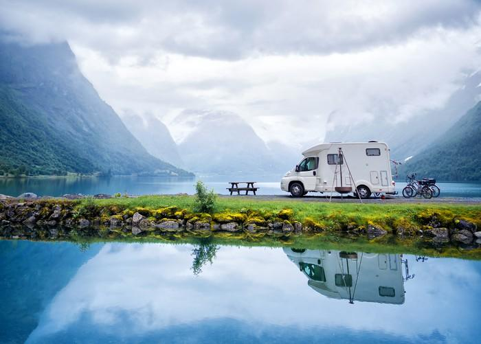 A camper parked in front of a mountain holiday scene.