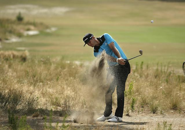 Dustin Johnson hits out of the native area on the 14th hole during the first round of the U.S. Open golf tournament in Pinehurst, N.C., Thursday, June 12, 2014. (AP Photo/Charlie Riedel)