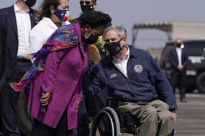 Rep. Sheila Jackson Lee, D-Texas, speaks with Texas Gov. Greg Abbott before greeting President Joe Biden and first lady Jill Biden at Ellington Field Joint Reserve Base in Houston, Friday, Feb. 26, 2021. (AP Photo/Patrick Semansky)