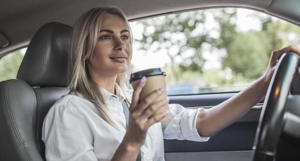Woman driving with a coffee. Source: Getty Images