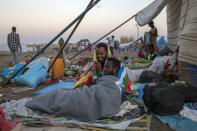 Tigray refugees who fled the conflict in the Ethiopia's Tigray sit up after waking up early morning at Hamdeyat Transition Center near the Sudan-Ethiopia border, eastern Sudan, Thursday, Dec. 3, 2020. Ethiopian forces on Thursday blocked people from the country's embattled Tigray region from crossing into Sudan at the busiest crossing point for refugees, Sudanese forces said.(AP Photo/Nariman El-Mofty)