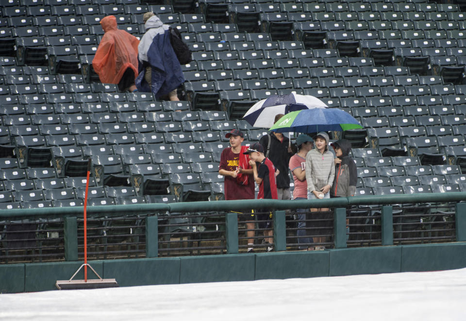 Die-hard Cleveland Indians fans hang out at Progressive Field after a baseball game against the Texas Rangers was called due to rain in Cleveland, Tuesday, Aug. 6, 2019. (AP Photo/Phil Long)