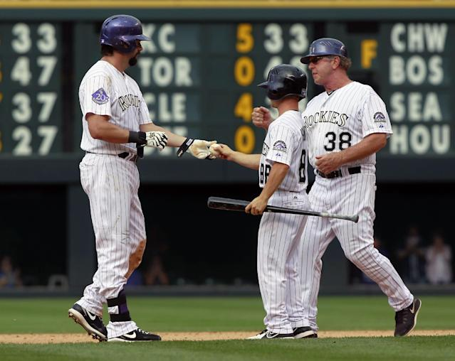 Colorado Rockies' Todd Helton, left, hands the ball to a batboy as first base coach Rene Lacheman, right, comes over to congratulate Helton after he hit a double for his 2,500th career hit against the Cincinnati Reds in the seventh inning of the Rockies' 7-3 victory in a baseball game in Denver on Sunday, Sept. 1, 2013. (AP Photo/David Zalubowski)