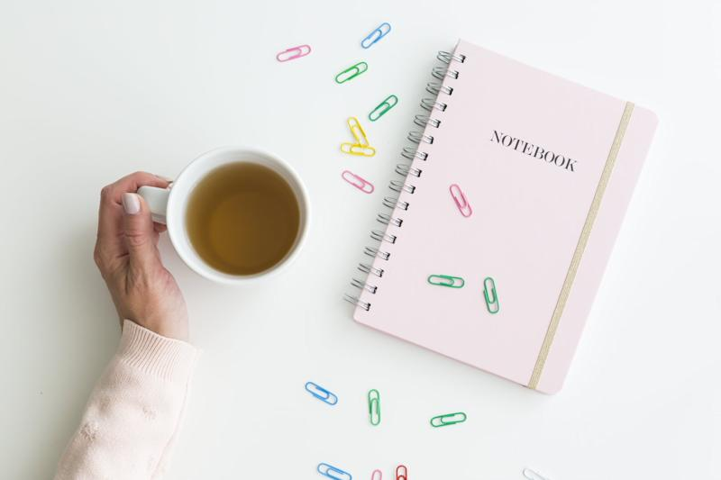 Woman holding a mug of hot fresh tea with her hand alongside a pink notebook with scattered colorful paperclips over white viewed from overhead