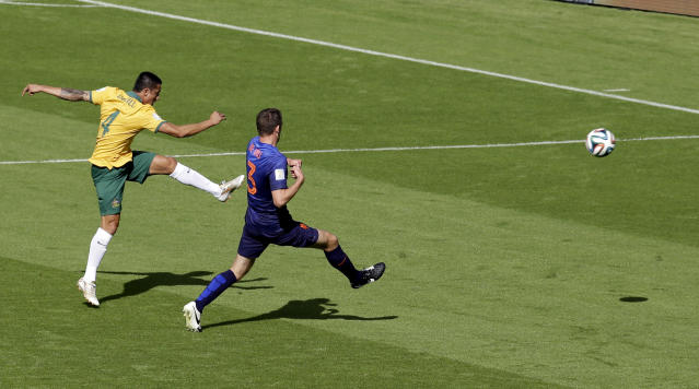 FILE - In this June 18, 2014 file photo, Australia's Tim Cahill, left, scores his side's first goal during the group B World Cup soccer match between Australia and the Netherlands at the Estadio Beira-Rio in Porto Alegre, Brazil. Shortly after Australia fell behind 1-0 down, Cahill ran onto to a looping pass from Ryan McGowan and hit a perfectly-timed volley with his weaker left foot from about 11 yards out. (AP Photo/Michael Sohn, File)