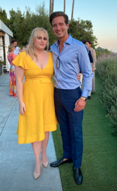 Rebel Wilson in a yellow dress with a male friend