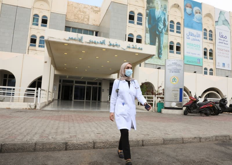 Israa Seblani, a Lebanese doctor and the bride who was caught up in the last year's Beirut port blast during a wedding photoshoot, walks outside Rafik Hariri University Hospital, in Beirut
