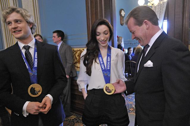 Senate Majority leader Randy Richardville, right, gets an up-close look at an Olympic gold medal as Michigan's olympic gold medal figure skaters, Charlie White, left, and Meryl Davis are honored at the Capitol on Tuesday morning, March 11, 2014, in Lansing, Mich. (AP Photo/Detroit News, Dale G. Young) DETROIT FREE PRESS OUT, MAGS OUT, MANDATORY CREDIT