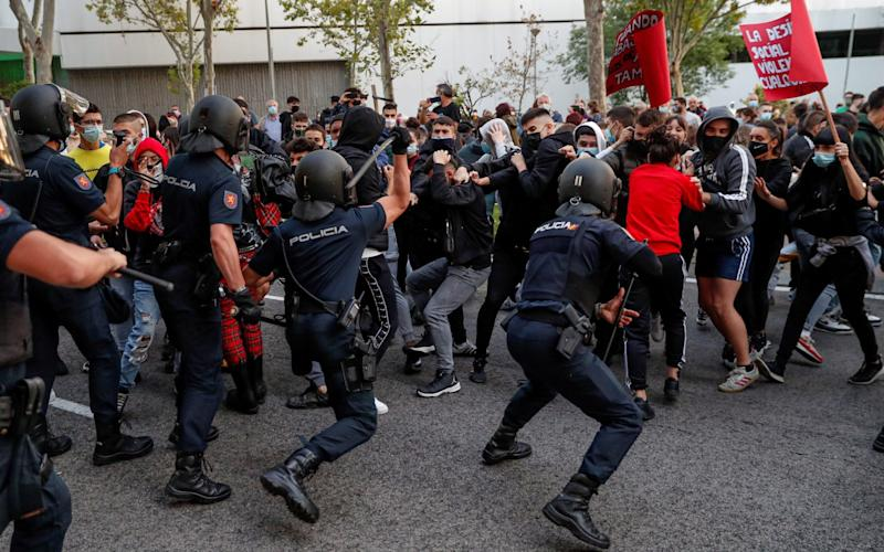 Police officers confront protesters next to the South Station, in Madrid, Spain, 24 September 2020, where dozens of people gathered to demand a better public health care and against the 'targeted' imposed lockdowns in the city. - Emilio Naranjo/EPA-EFE/Shutterstock