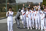 Japanese torchbearer Azusa Iwashimizu, left, a member of Japan women's national football team, smiles after passing the flame to the next torchbearer during the torch relay grand start outside J-Village National Training Center in Naraha, Fukushima prefecture, northeastern Japan, Thursday, March 25, 2021. The torch relay for the postponed Tokyo Olympics began its 121-day journey across Japan on Thursday and is headed toward the opening ceremony in Tokyo on July 23. (Philip Fong/Pool Photo via AP)