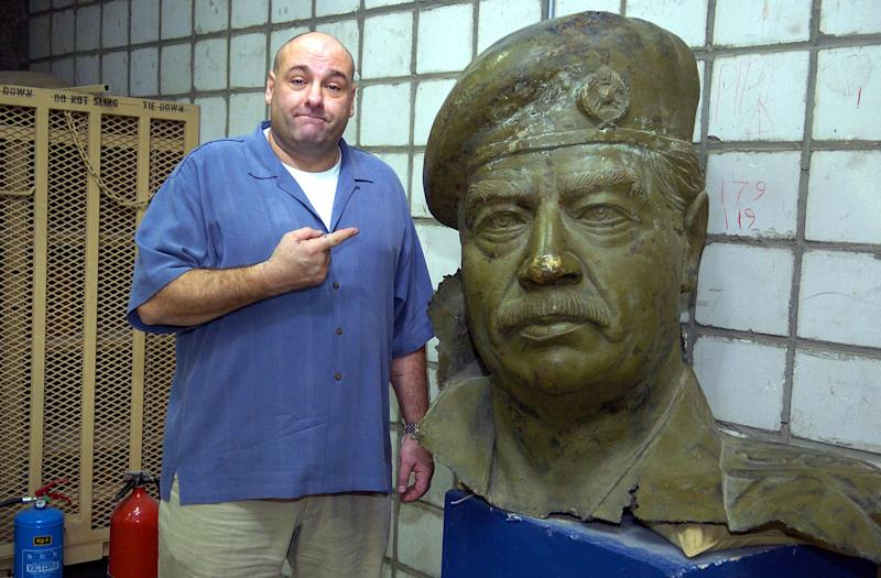 "FILE - In this Nov. 16, 2004 file photo supplied by the USO, James Gandolfini, poses with a bust of Saddam Hussein during a visit to Camp Doha, Kuwait,on Tuesday, November 16, 2004. Gandolfini and fellow actor Tony Sirico, who plays Paulie Walnuts in the series, visited U.S. troops in Kuwait and Iraq sponsored by the United Service Organizations. Gandolfini, whose portrayal of a brutal, emotionally delicate mob boss in HBO's ""The Sopranos"" helped create one of TV's greatest drama series and turned the mobster stereotype on its head, died Wednesday, June 19, 2013 in Italy. He was 51.(AP Photo/USO, Mike Theiler, File)"